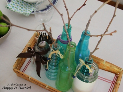 Simple Centerpiece with colored bottles and twigs in Table Setting